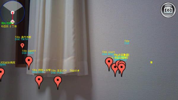 TravelCamerAR -トラベルカメラ-:距離感がわかる目的方向の施設名が表示され、左上には方位が表示されています
