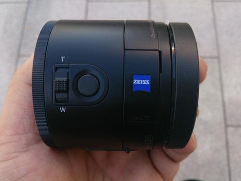 「QX100」。ズームとシャッターボタンも搭載されている